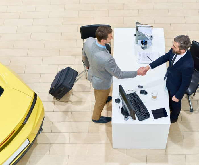 Above view of handsome businessman shaking hands with car salesman over table after renting luxury car for business travelling, copy space