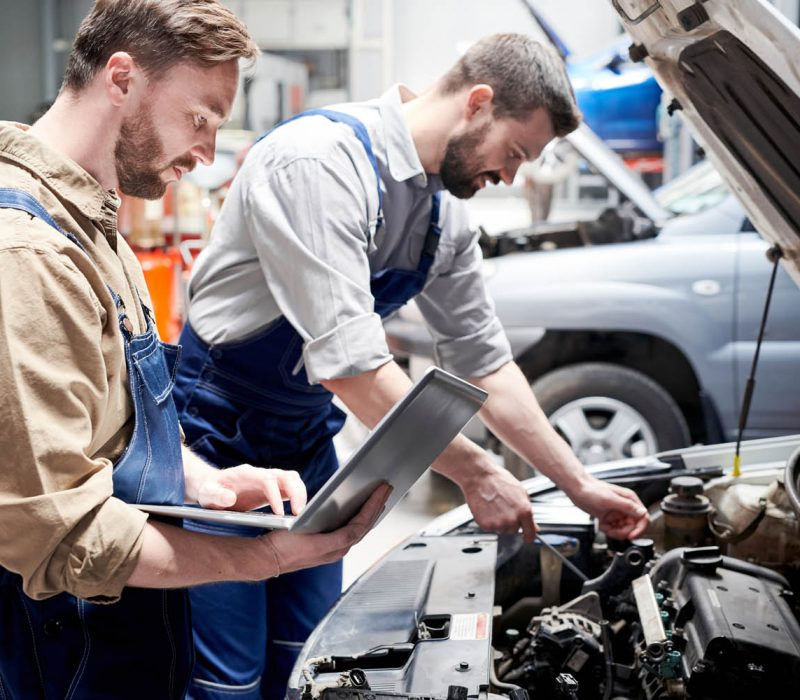 Side view portrait of two modern bearded mechanics looking under hood of car inspecting engine and using laptop  while working in car service and repair center, copy space